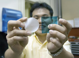 Ho Bum Park holding two samples of the chlorine-tolerant, desalination membrane