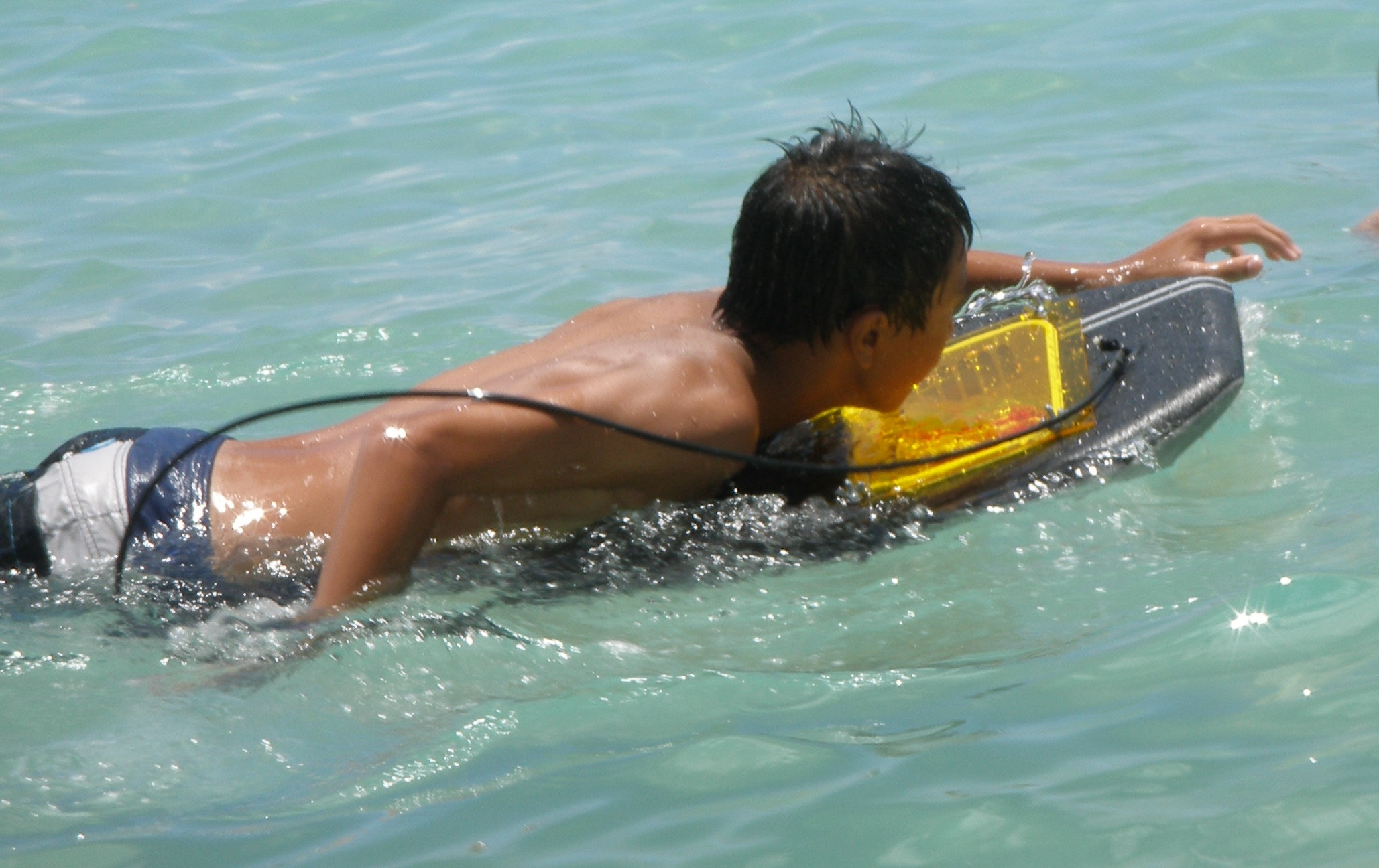 Boy surfing on photochemical reactor surfboard in Hawaii