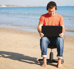A man using a laptop with headphones on a beach