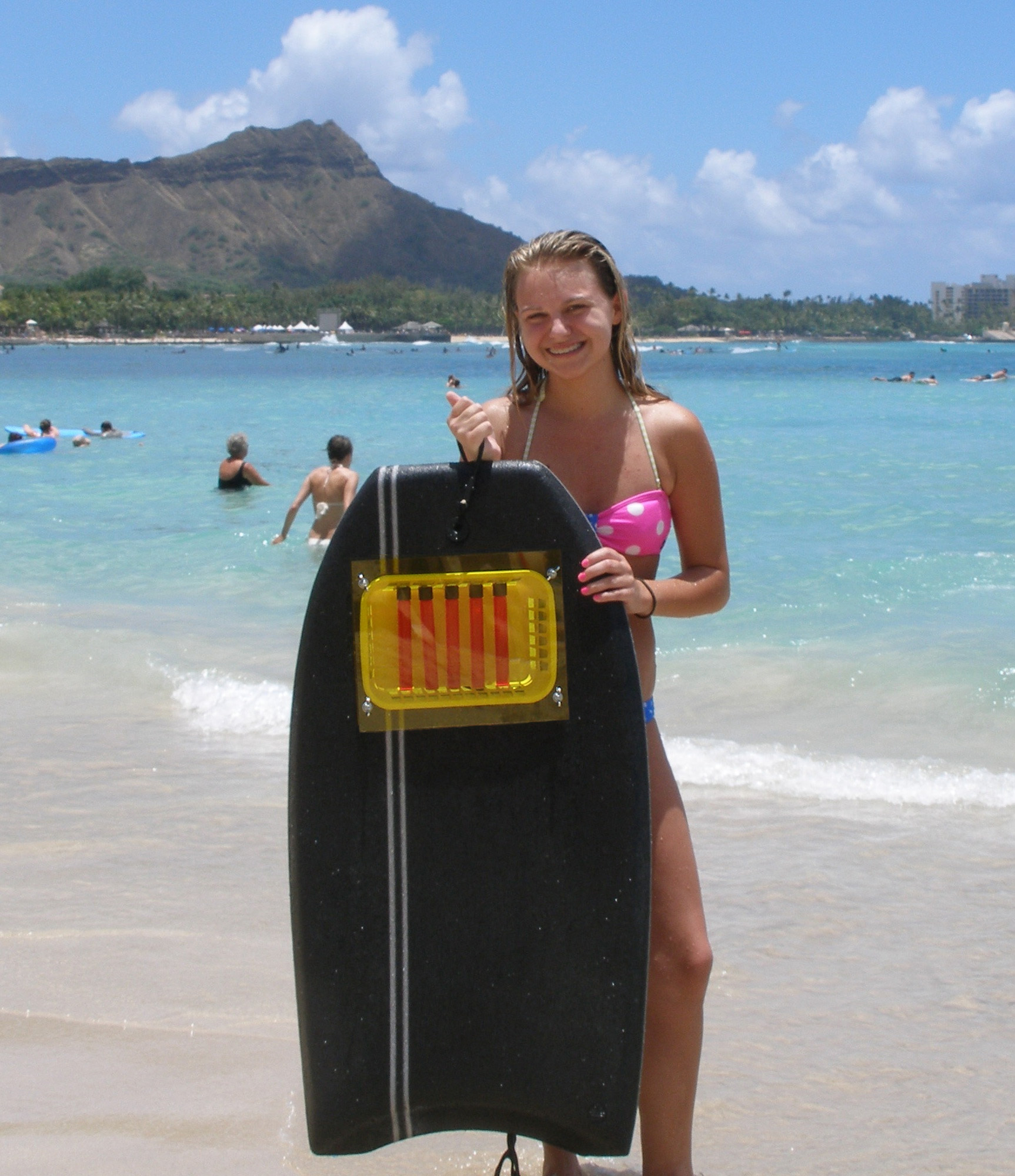 Girl holding photochemical reactor surfboard on beach in Hawaii